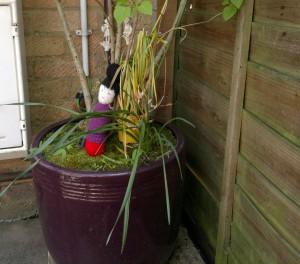 Doll in flower pot