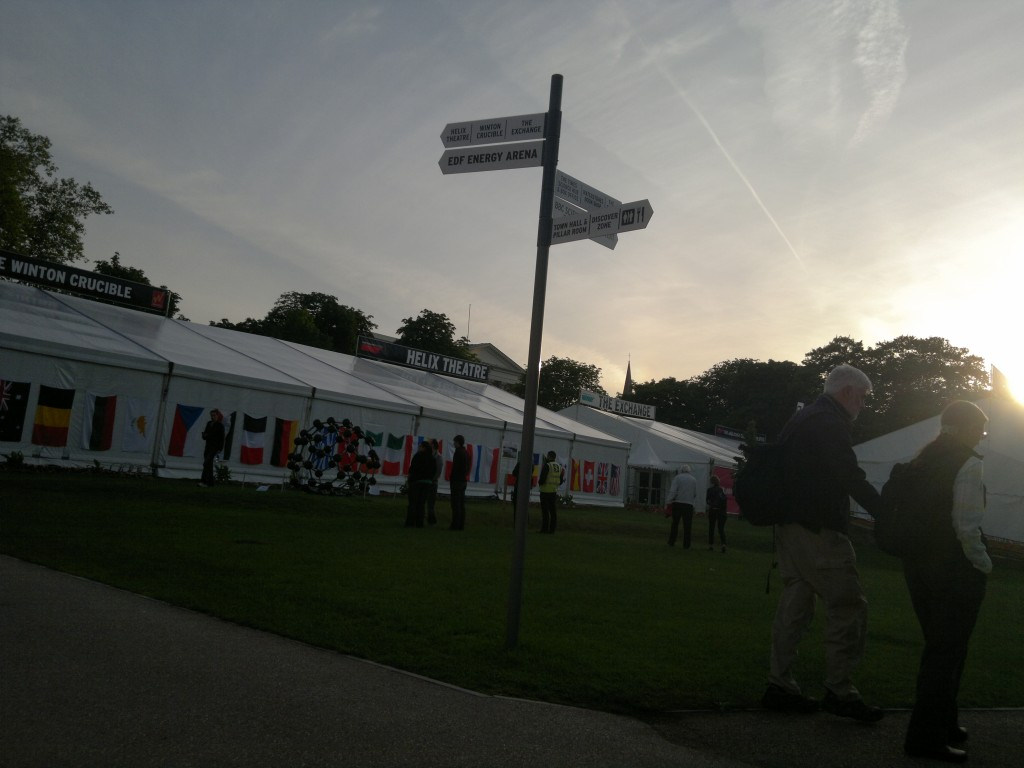 Picture of a sign with tents behind and sun low in the sky