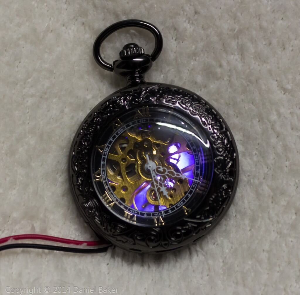 A pocket watch with a blue glow shining through for cosplay