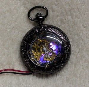 A pocket watch with a blue glow shining through