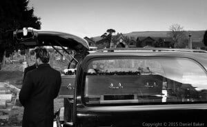 black and white photo of a funeral casket being lifted out of the back of a hearse
