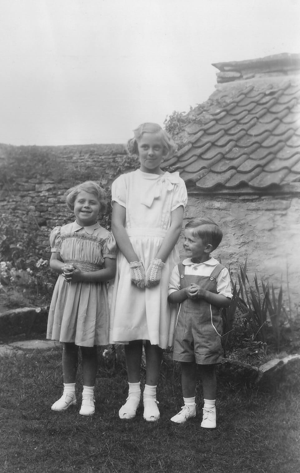 three children in old fashioned clothes, standing together in a garden, the middle child is a tall girl in a white dress with blonde hair.