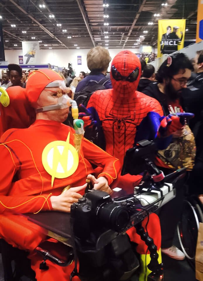 A picture of me in my wheelchair dressed as The Flash with a Spiderman cosplayer