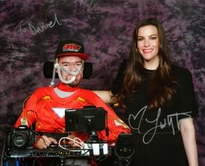Liv Tyler in black dress standing next to me in my wheelchair with Iron man top and Stark Industries baseball cap