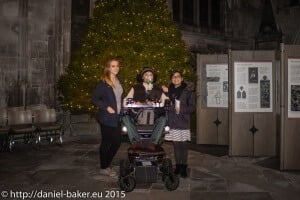 Daniel baker inbetween two women in front of a huge Christmas inside Gloucester Cathedral
