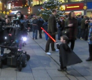 Me in my wheelchair dressed as Darth Vader with a two year old boy also dressed as Darth Vader attacking with his red light Saber
