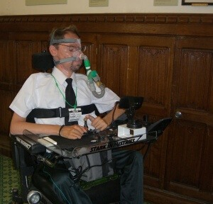 Mr Baker in his wheelchair sitting in front of a wood panelled wall inside parliament