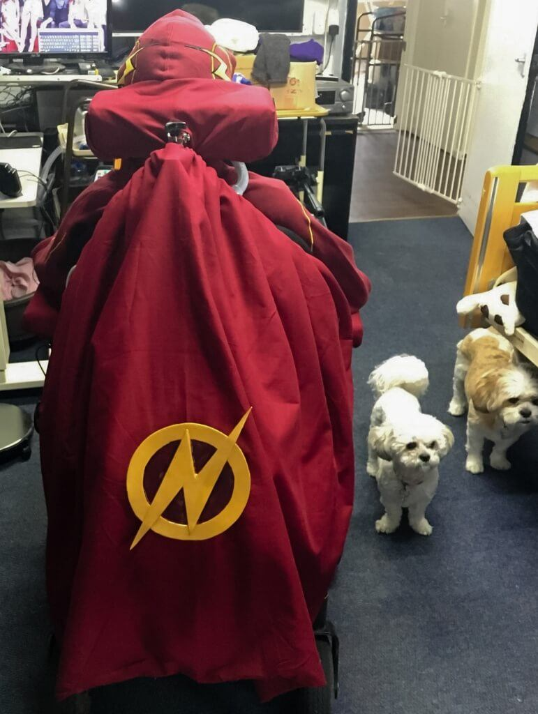 MCM London 2016 Cosplay Preview Burgundy cape with The Flash logo attached to the back of a wheelchair