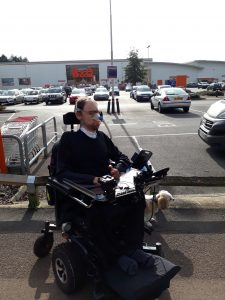 Daniel Baker outside B&Q in his wheelchair with his dog Mya