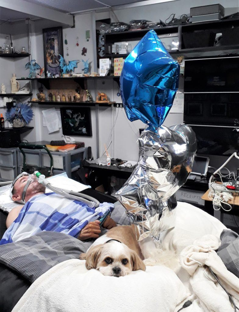 Mya a cavatsu lying on a bed with Daniel Baker and three metallic balloons floating above her, one blue, two silver