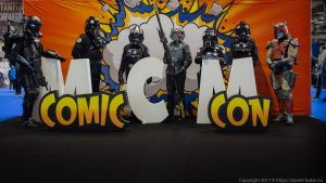 Various Star Wars characters in cosplay standing behind the MCM comiccon logo