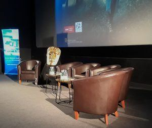 BAFTA mask next to a brown leather sofa in front of a large cinema screen