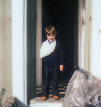 Daniel Baker wearing his school uniform, standing in the doorway of his home with his right arm in a sling