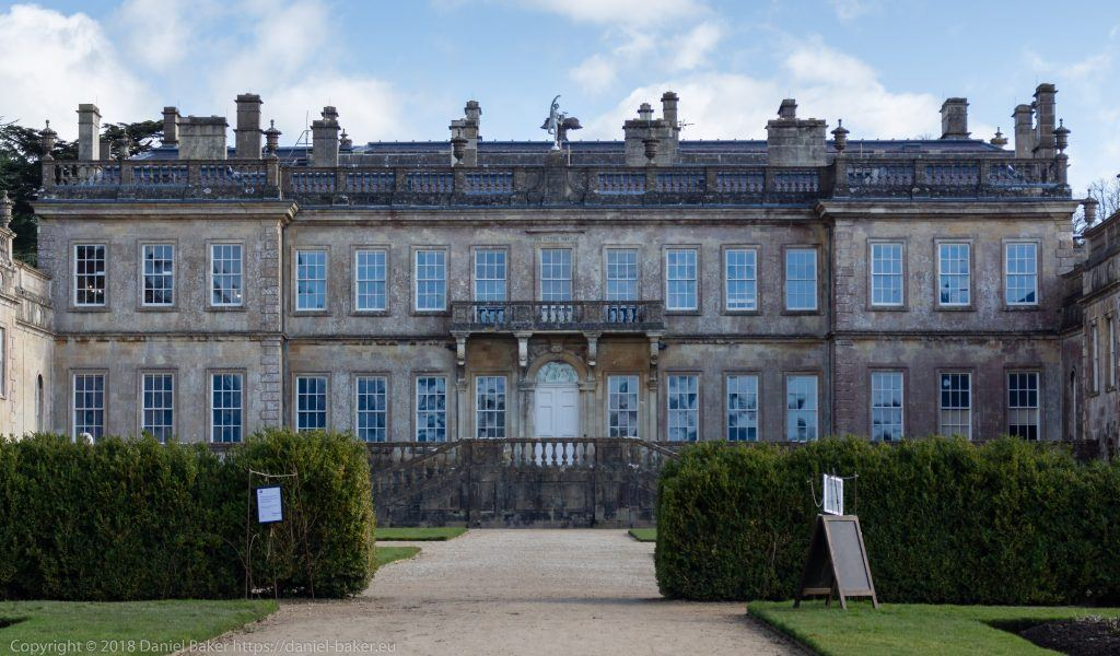 Dyrham Park House, a large manor house viewed from the garden with blue sky and a few white clouds above