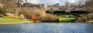 view across the lake and landscaped garden to the small waterfall at Dyrham Park
