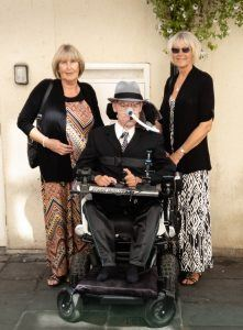 Daniel sitting in his wheelchair with his Aunt and Mother standing either side dressed up ready to watch The Price