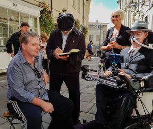Brenden Coyle sitting and chatting with Daniel with David Suchet in the background signing an autograph with Daniel's Aunt beside him