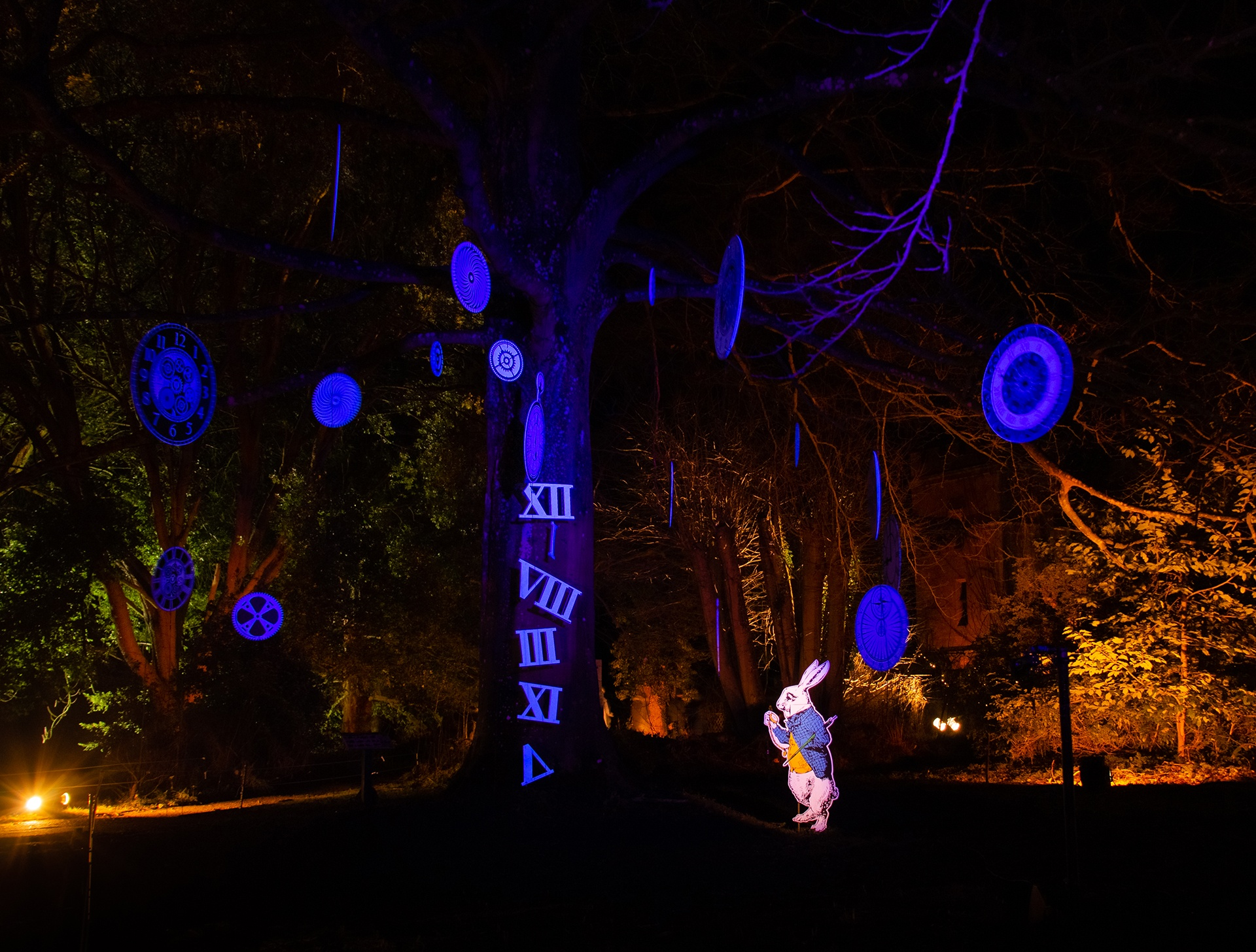 A lit up tree with clocks attached to it and a white rabbit in a suit looking at it at the Sudeley Castle Spectacle of Light