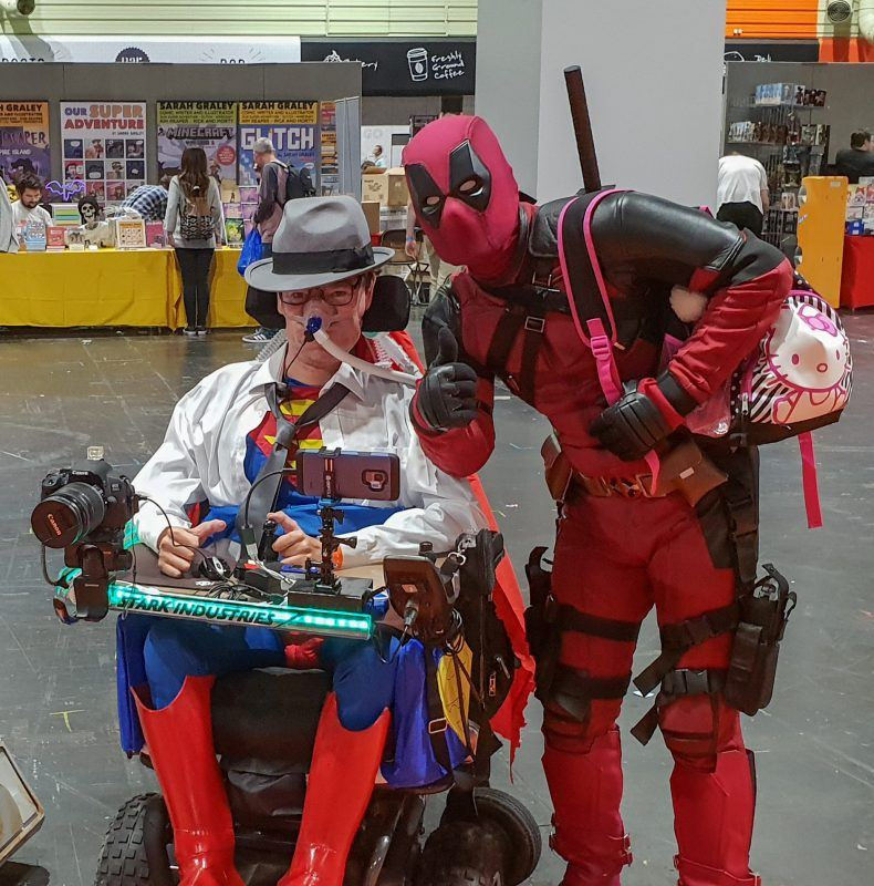 Daniel Baker in his wheelchair dressed as Clark Kent/Superman with Deadpool beside him