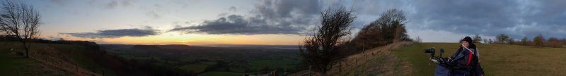 a panorama of a sunset with Daniel Baker looking out over it