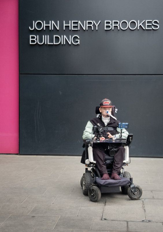 Daniel Baker in his wheelchair sitting in front of the John Henry Brookes building