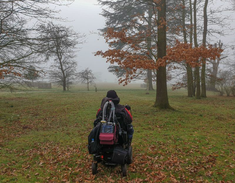 Daniel Baker in his wheelchair facing into the fog in woodland