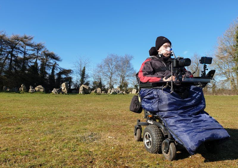 Daniel Baker in his wheelchair sitting in front of a neolithic stone circle