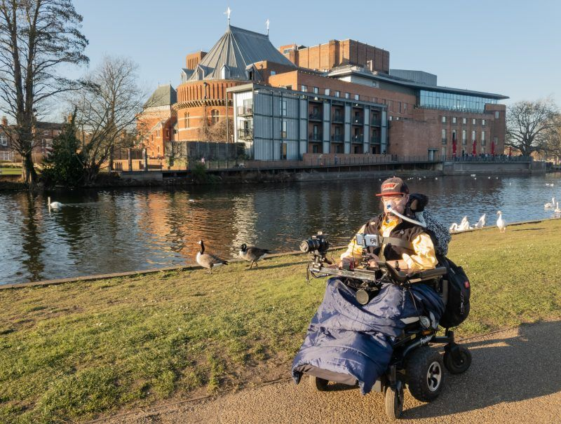 Daniel Baker in his wheelchair next to the River Avon, with the Shakespeare Royal Theatre across the river behind him