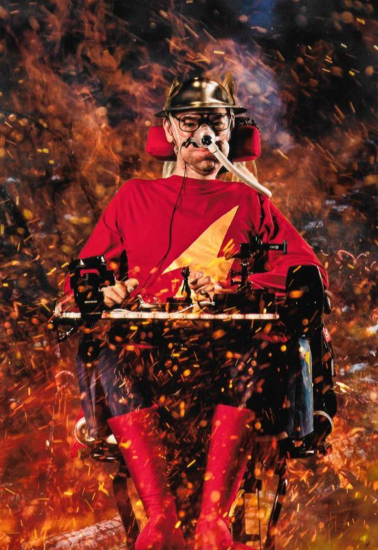 Picture of Daniel Baker in his wheelchair dressed as Jay Garrick surrounded by flames at Mcm Comiccon Birmingham 2019