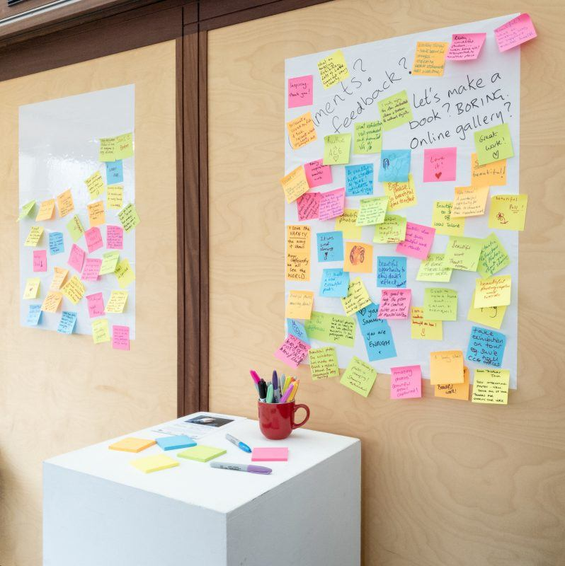 lots of fluorescent post it notes stuck on a board with positive feedback written on them
