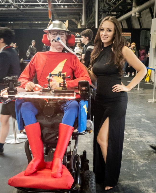Daniel Baker in his wheelchair dressed as Jay Garrick with Tabitha Lyons in a long black dress standing beside him at Mcm Commiccon Birmingham 2019