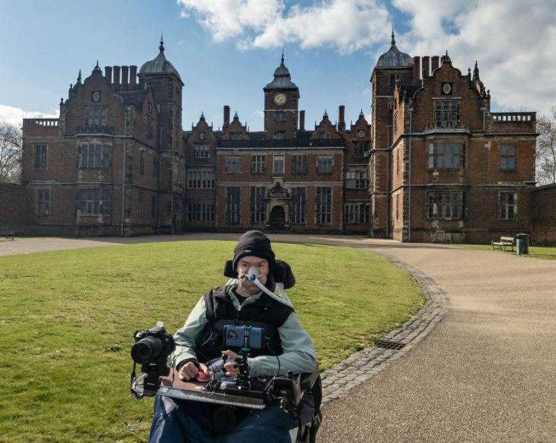 Daniel Baker in his wheelchair sitting in front of Aston Hall