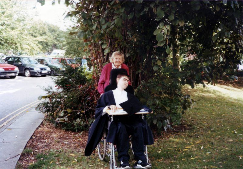 Daniel Baker in his graduation gown sitting outside Oxford Brookes University with his Nan Olive Baker standing behind him