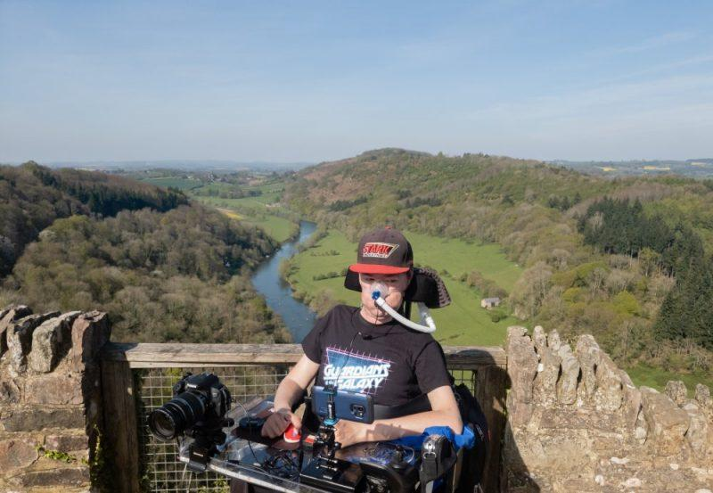 Easter Weekend - Daniel Baker in his wheelchair wearing a Guardians of the Galaxy T-Shirt at the top of Symonds Yat, with a view of hills and a winding river behind him