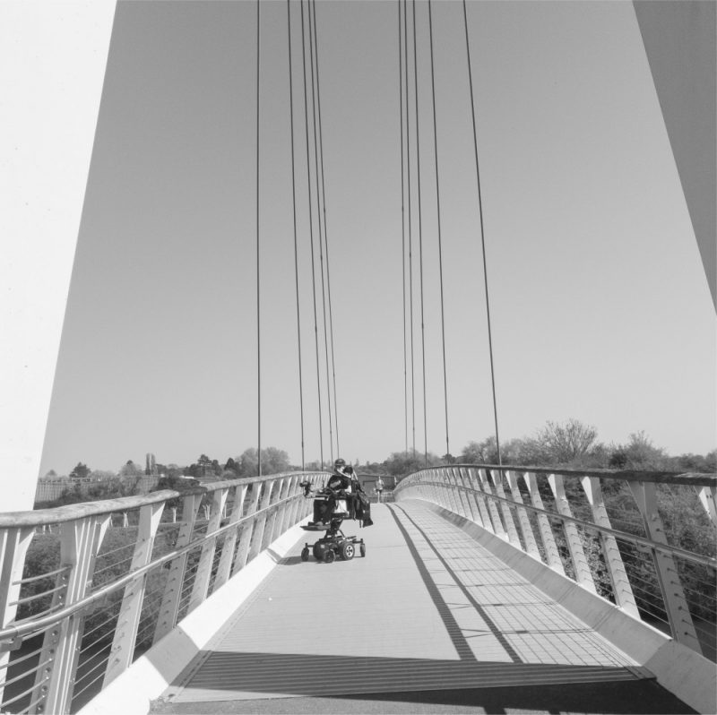Easter Weekend Black and White image of Daniel Baker in the distance sitting in his wheelchair on a suspension bridge over Worcester canal