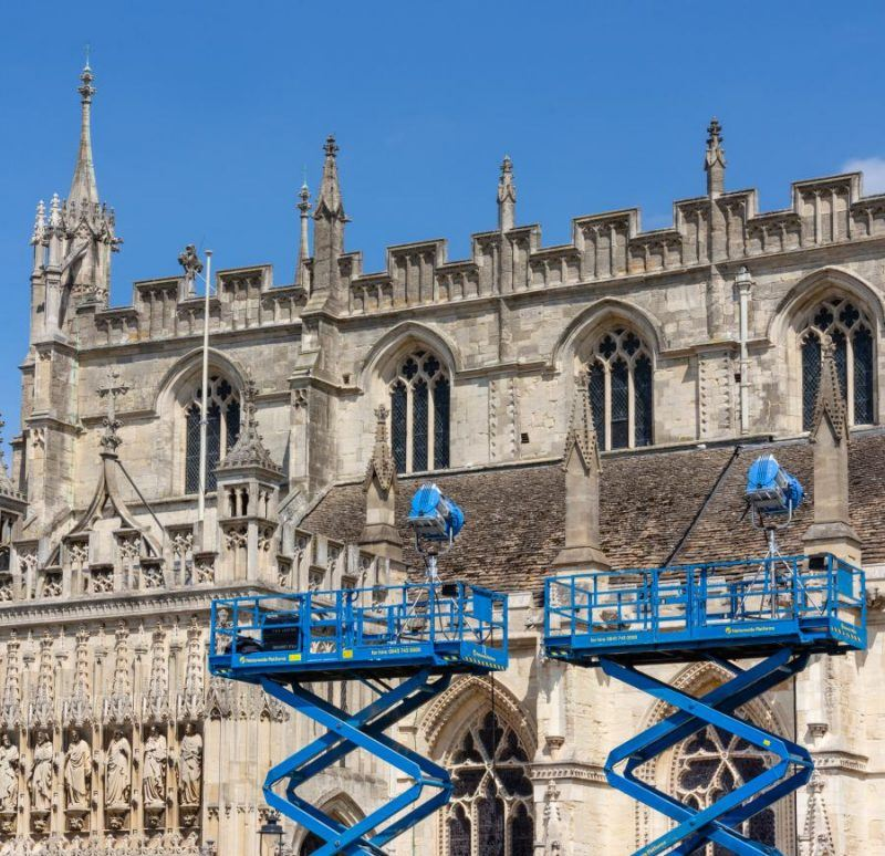 Blue metal hydraulic platforms supporting spotlights in front of Gloucester Cathedral