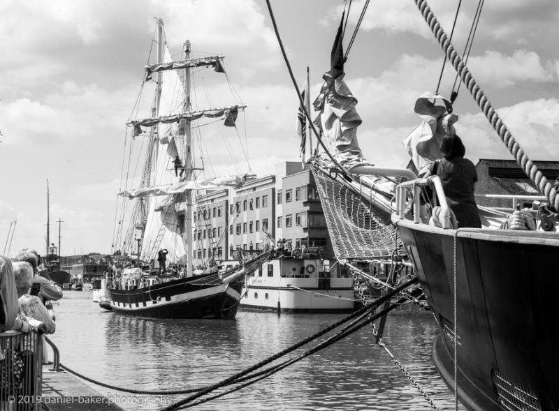 A black and white photo of a sailed tall ship entering Gloucester Docks