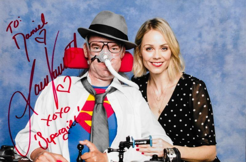 Collage of Daniel Baker at Collectormania 26 wearing a Superman/Clark Kent cosplay next to Laura Vandervoort, copyright Showmasters