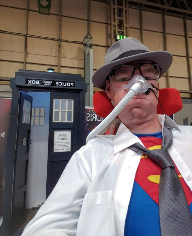 Daniel Baker at Collectormania 26 wearing a Superman/Clark Kent cosplay in front of a TARDIS