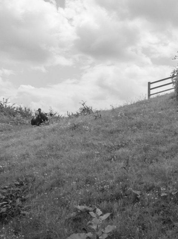 Black and white photo of Daniel Baker driving up a steep hill in his wheelchair