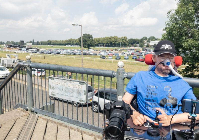 """Daniel Baker sitting on a bridge overlooking Worcester raceecourse, wearing a blue big bang theory t-shirt which reads """" Don't you think if I was wrong I'd know it?"""""""