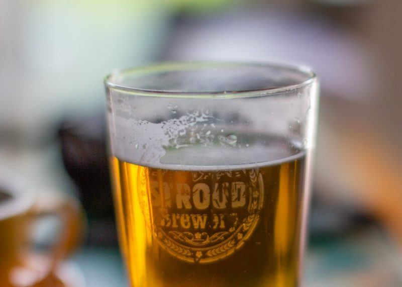 a close up photo of a pint of beer with Stroud Brewery written on the glass