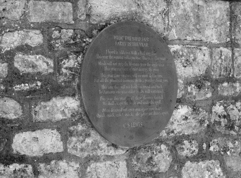 Plaque which reads I heard in Addison's Walk a bird sing clear: This year the summer will come true. This year. This year. Winds will not strip the blossom from the apple trees This year, nor want of rain destroy the peas. This year time's nature will no more defeat you, Nor all the promised moments in their passing cheat you. This time they will not lead you round and back To Autumn, one year older, by the well-worn track. This year, this year, as all these flowers foretell, We shall escape the circle and undo the spell. Often deceived, yet open once again your heart, Quick, quick, quick, quick!—the gates are drawn apart.