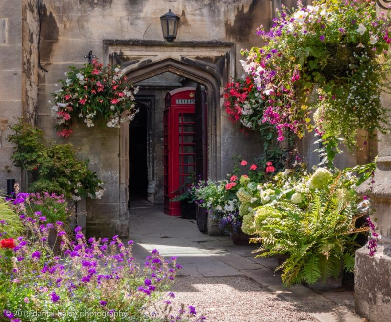 An archway surrounded by flowers, just beyond in a nook can be seen an old fashioned red phone box