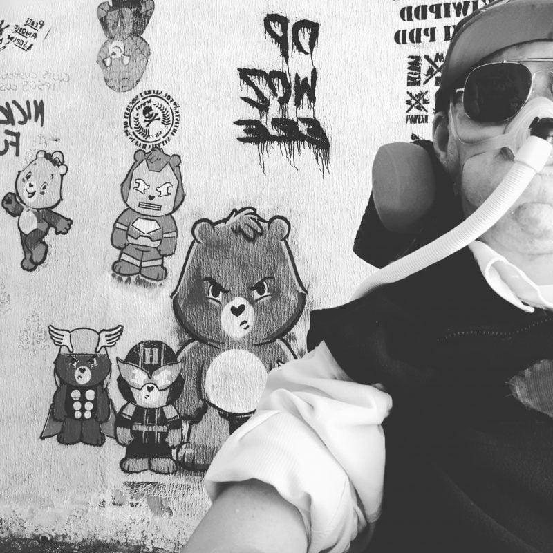 Daniel in front of care bear graffiti