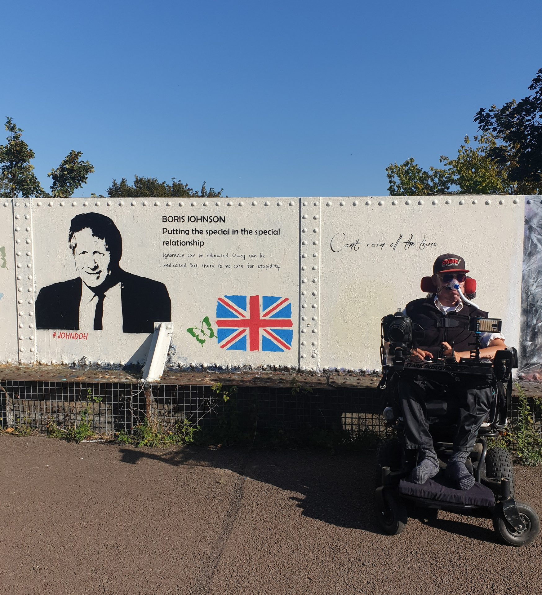 Daniel Baker in front of some graffiti about BorisJohnson