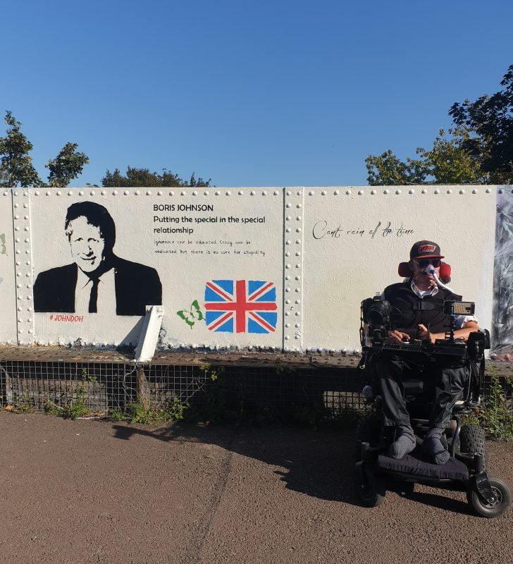 Daniel Baker in front of some graffiti about BorisJohnson
