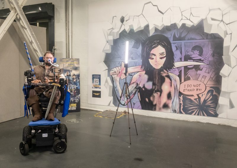 Daniel Baker in a knight (Galavant) cosplay with a mural behind him