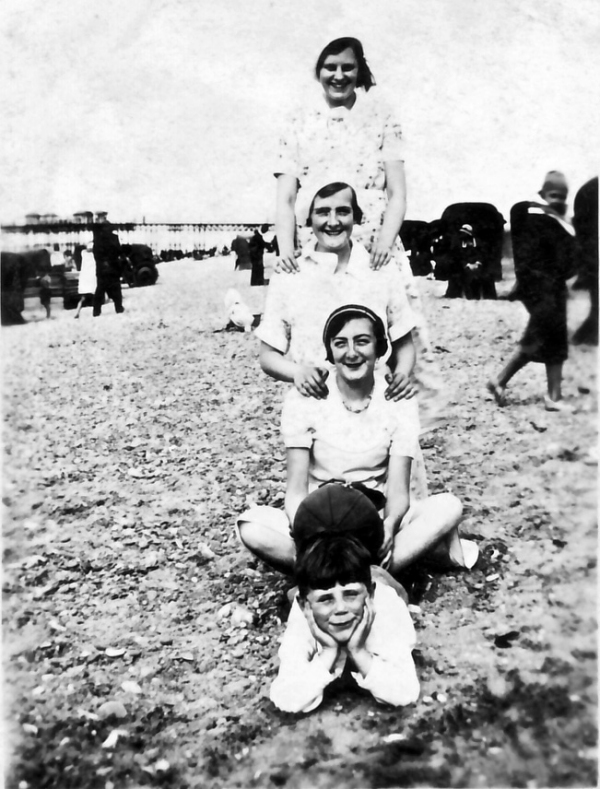 black and white photo of four people one behind the other facing the camera on a beach