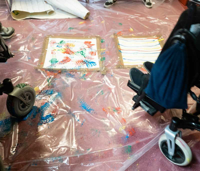 Painting using wheelchair wheels Close up of red and blue boardgame pieces at DMD Pathfinders Christmas Party held at Helen and Douglas House